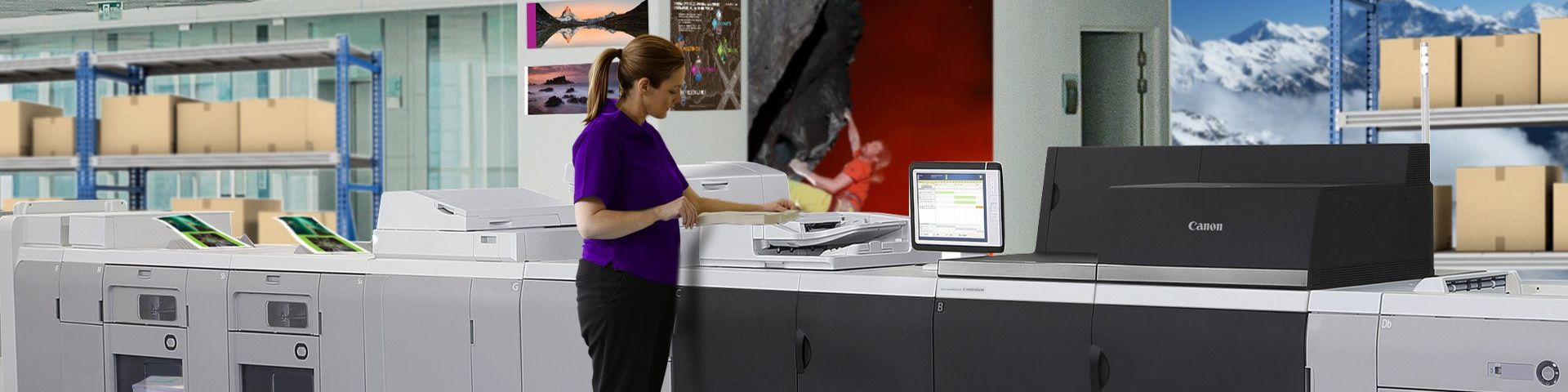 A woman in a purple top is operating a long black and grey Canon professional grade printer. Behind the machine are racks with cardboard boxes on them.